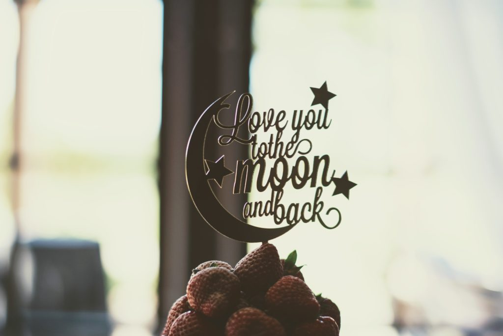 "Cake topper states ""Love you to the moon and back"""
